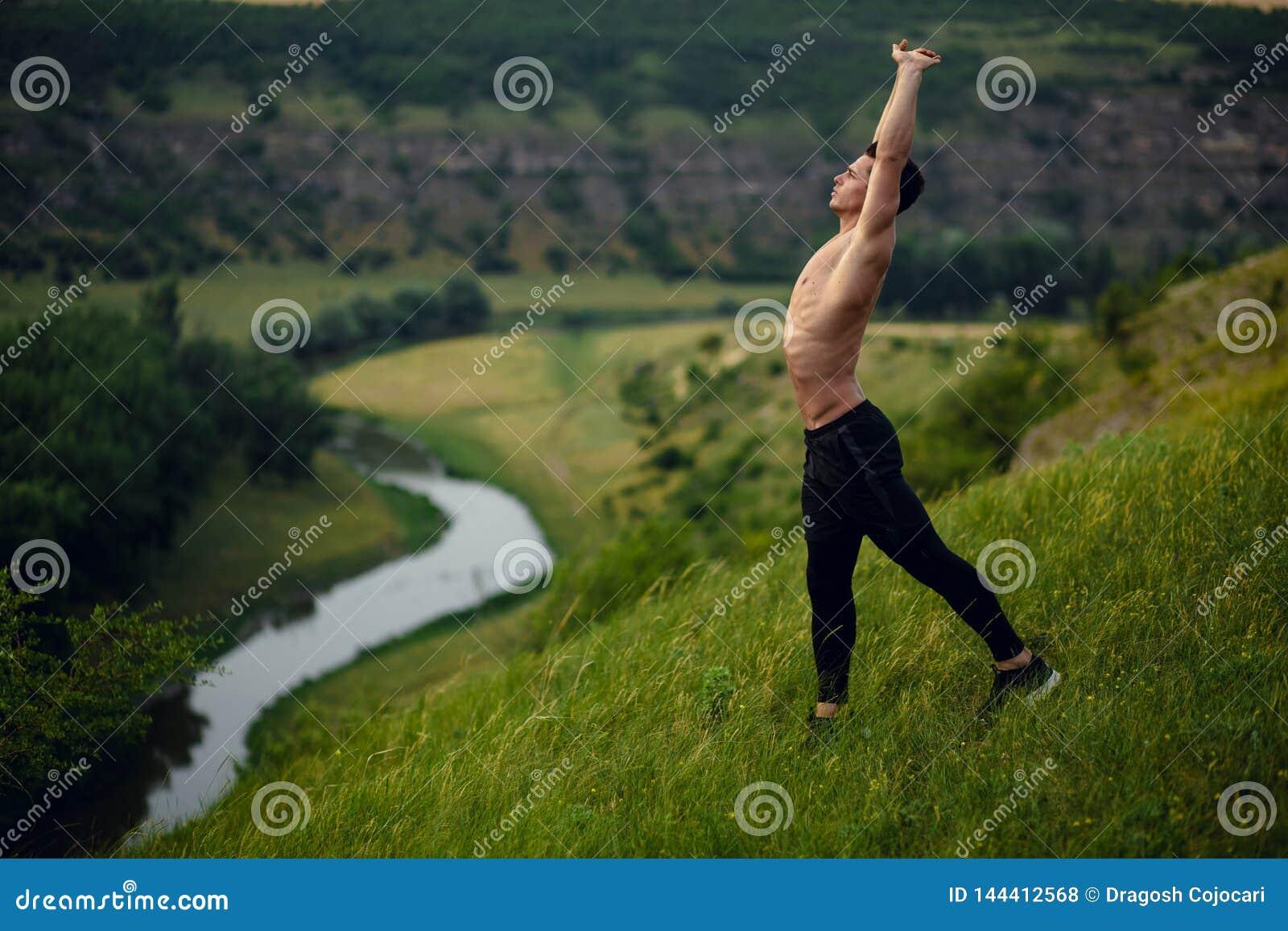 Un jeune homme convenable folâtre sans chemise faisant étirant des exercices extérieurs sur le fond de paysage Vue horizontale