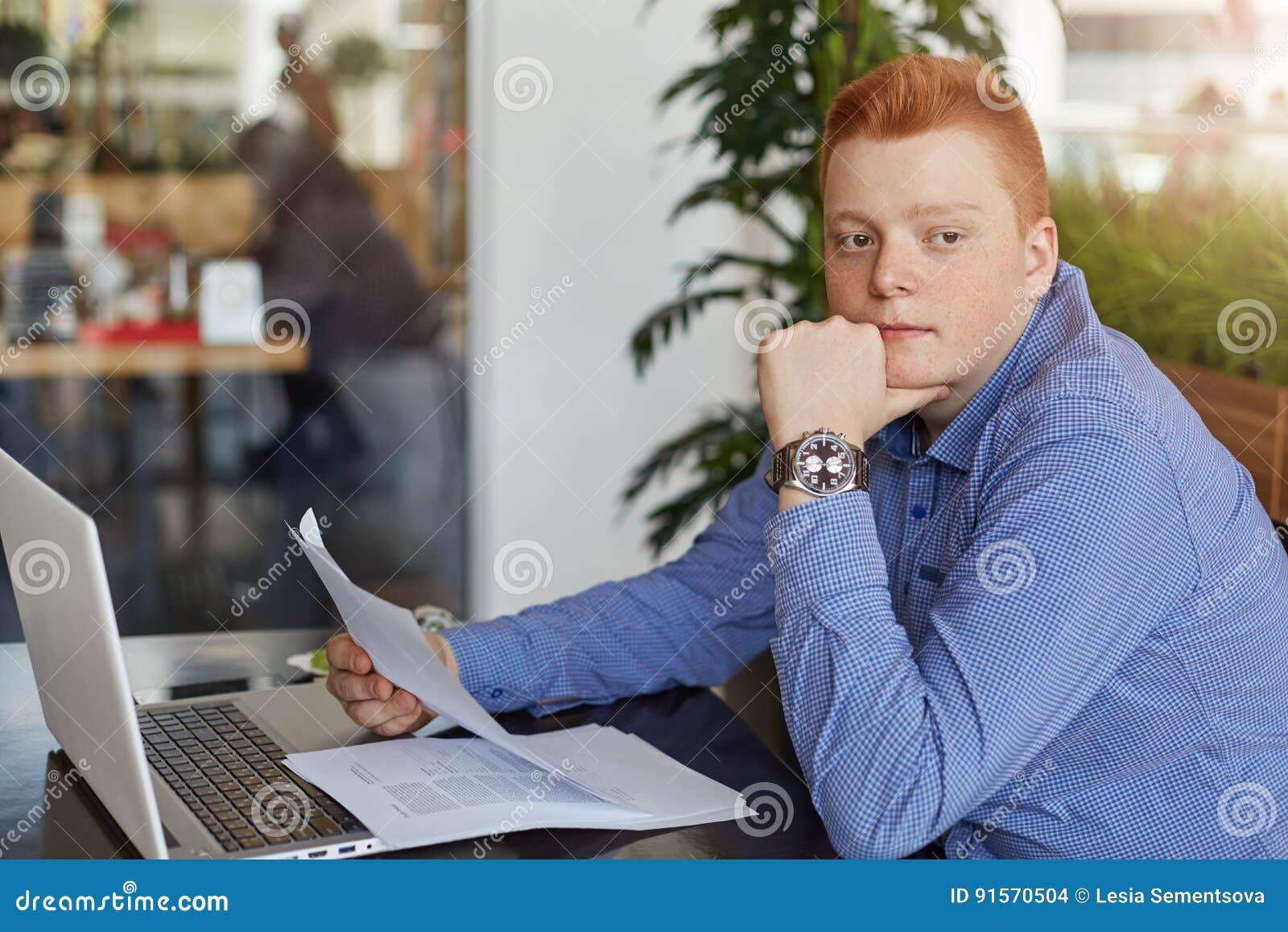 Un jeune homme d affaires roux songeur utilisant la chemise formelle se reposant à la table avec l ordinateur portable et aux doc