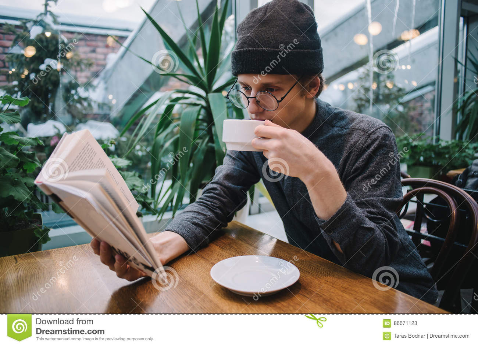 Un jeune homme dans un chapeau et une chemise lisant un livre et buvant du café dans un restaurant avec le conservatoire