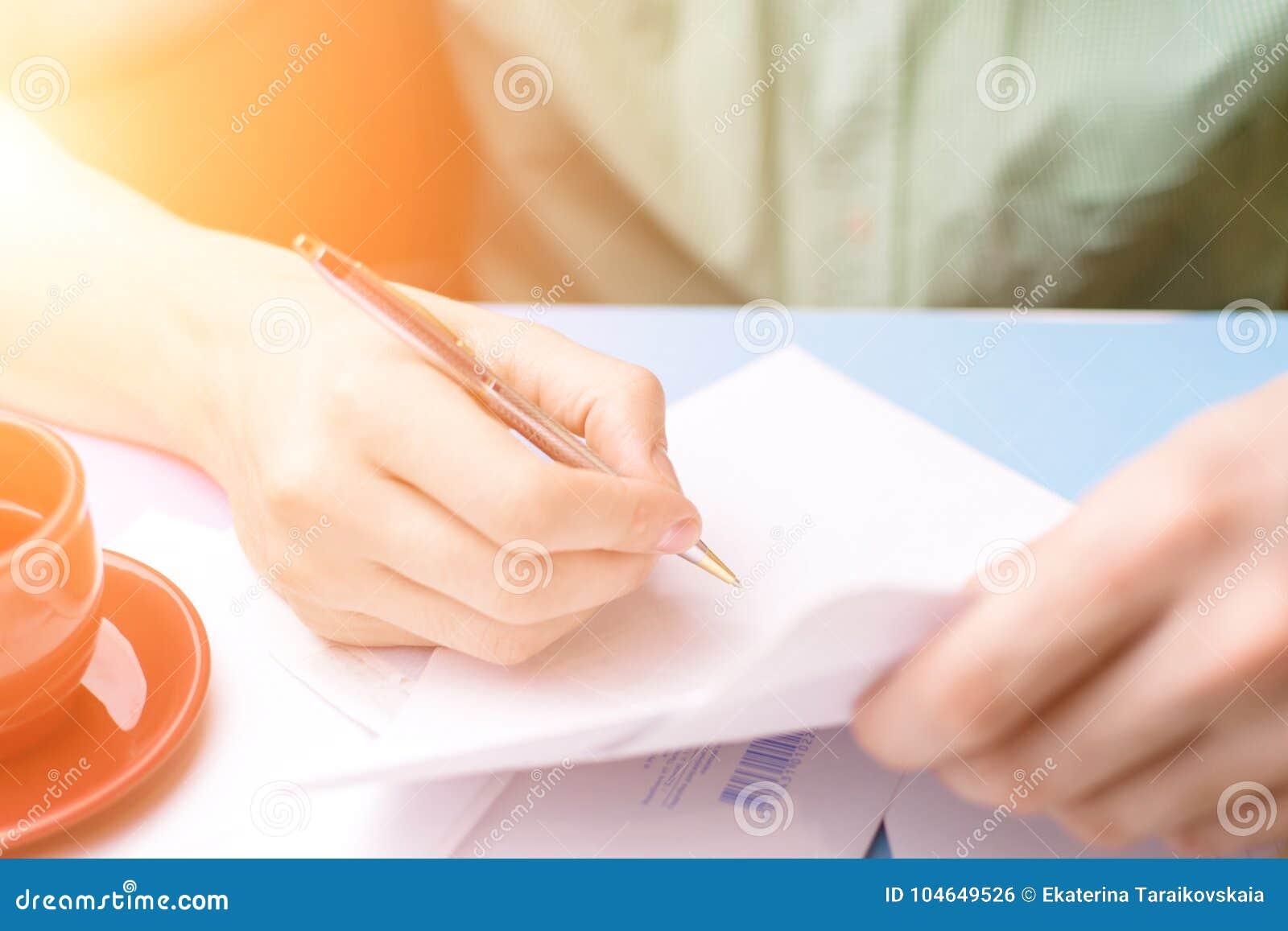 Un jeune homme examine et signe la lettre Le concept de la correspondance