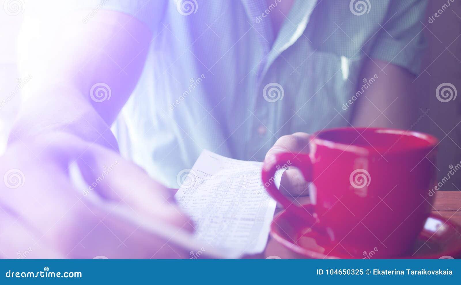 Un jeune homme examine la facture dans un café un matin ensoleillé d été