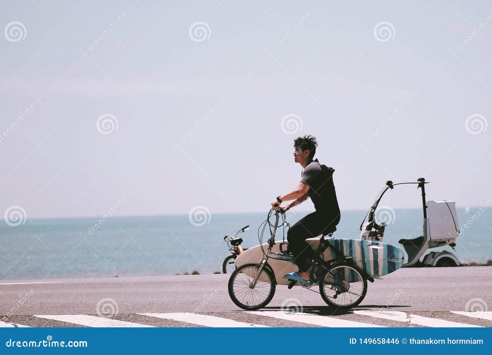 Un jeune homme faisant du vélo pour surfer à la mer