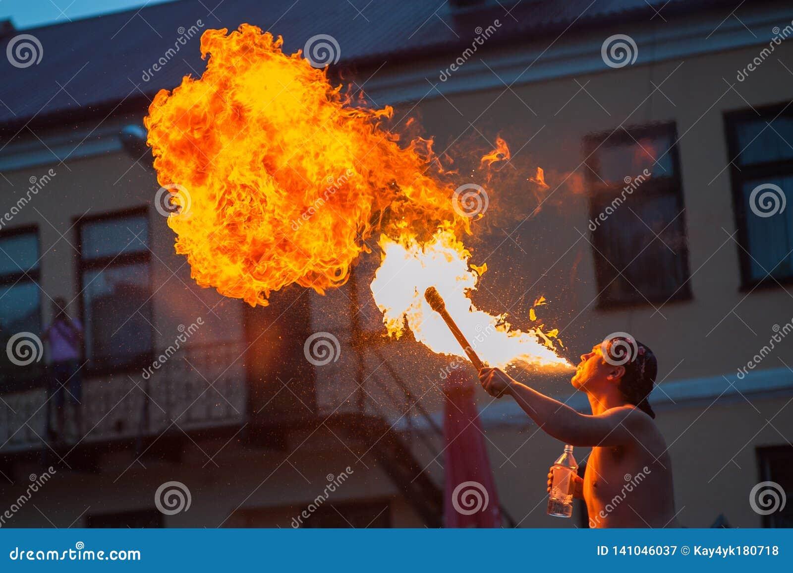 Un jeune homme répand un feu hors de son jeune homme de mouththe répand le feu de sa bouche spectacle pour des visiteurs