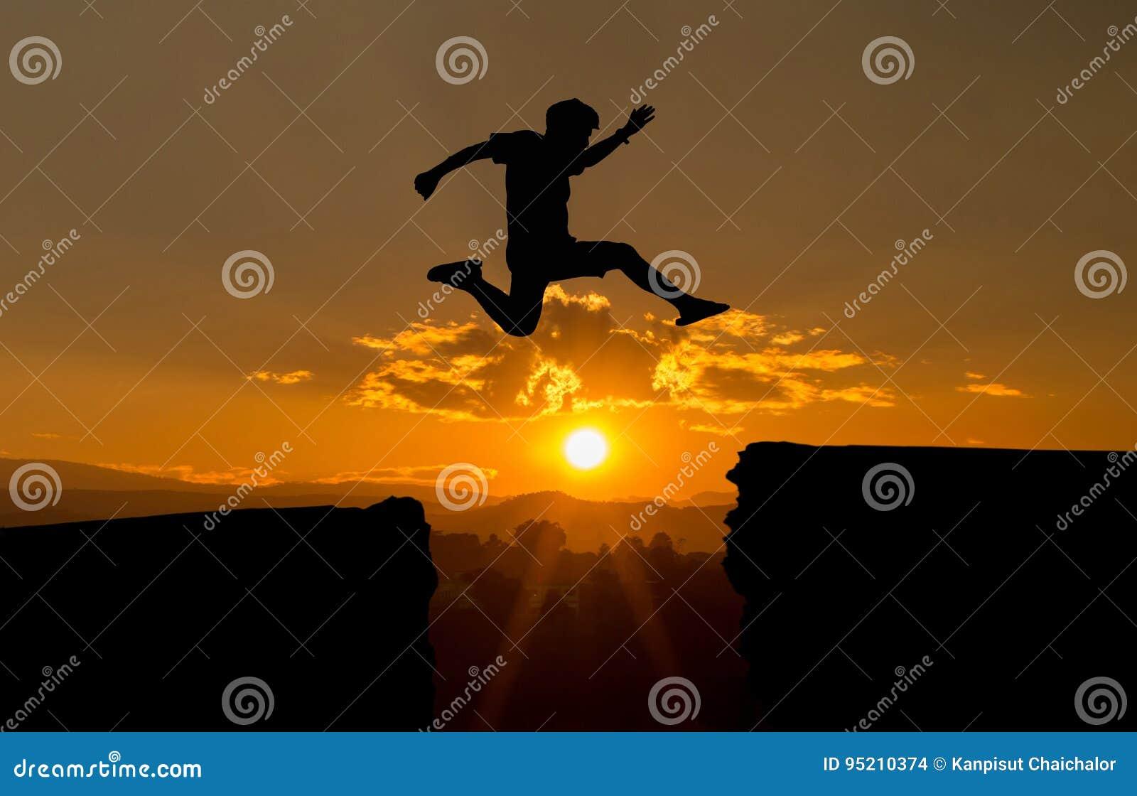 Un jeune homme sautent entre 2017 et 2018 ans au-dessus du soleil et sur l espace de la silhouette de colline égalisant le ciel c