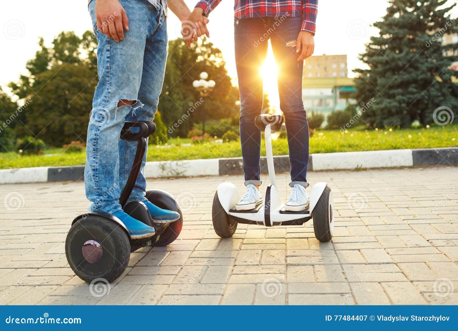 Un jeune hoverboard d équitation de couples - scooter électrique, personnel