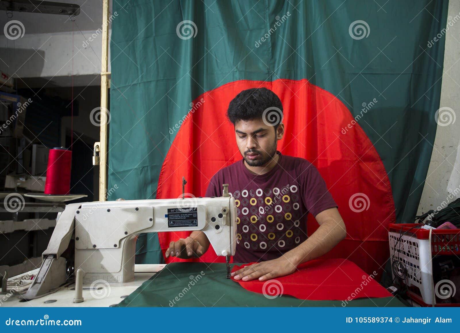 Un jeune tailleur Md Rashed Alam, vieillissent 28 drapeaux nationaux bangladais de fabrication chez Dhaka, Bangladesh