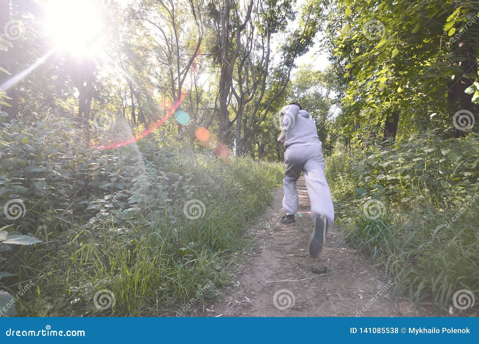 Un jeune type dans un costume gris de sports court le long du chemin parmi