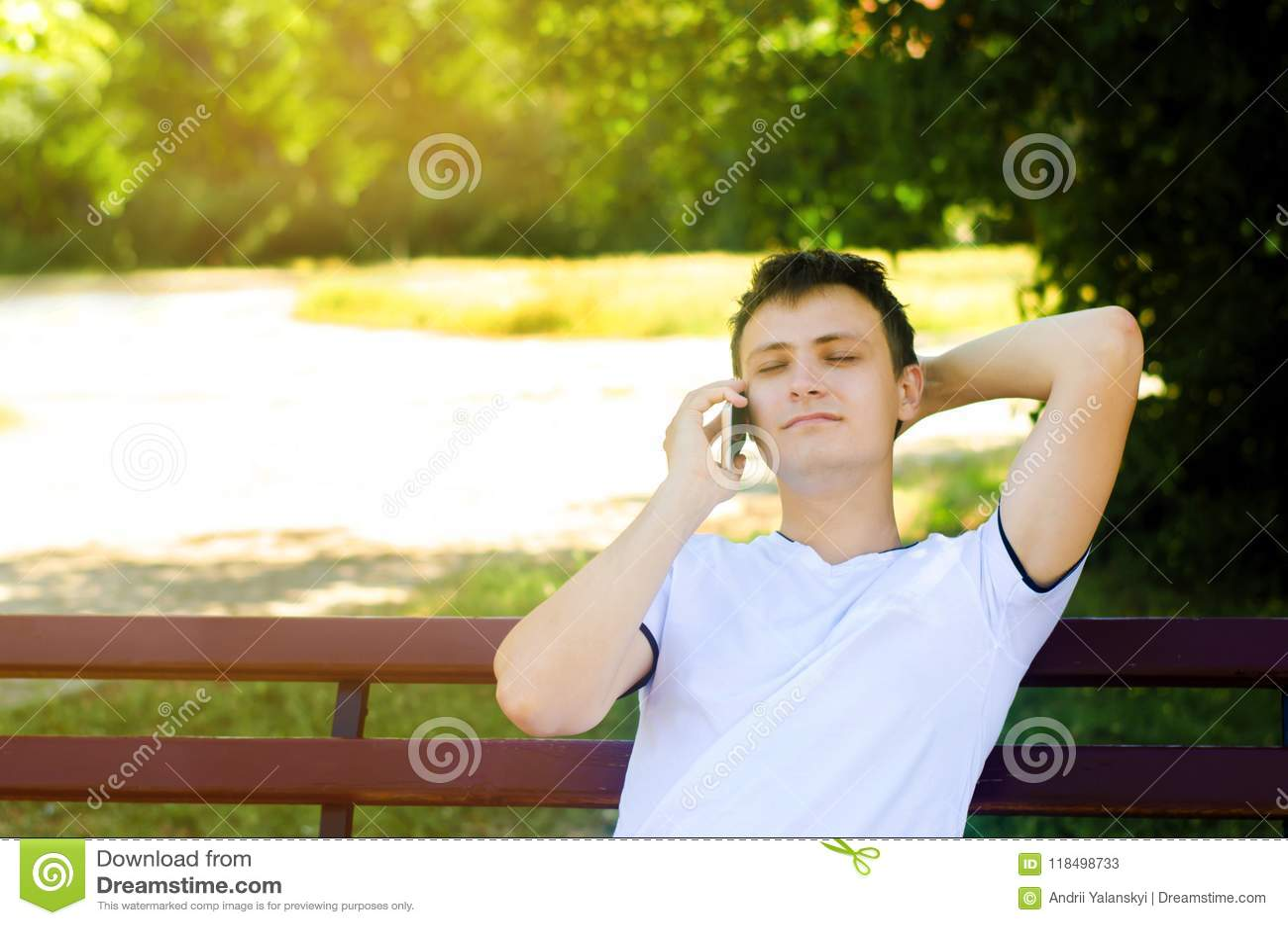 Un jeune type européen s assied sur un banc en parc et parle au téléphone, jetant son bras derrière sa tête et fermeture le sien