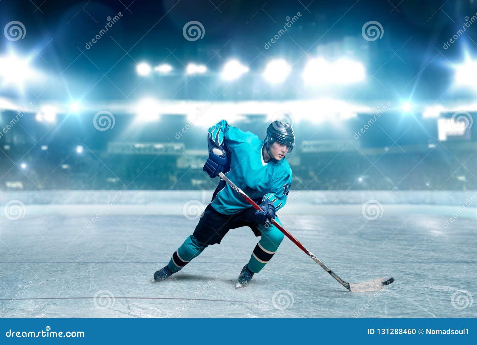 Un joueur de hockey patinant avec le bâton sur l arène de glace