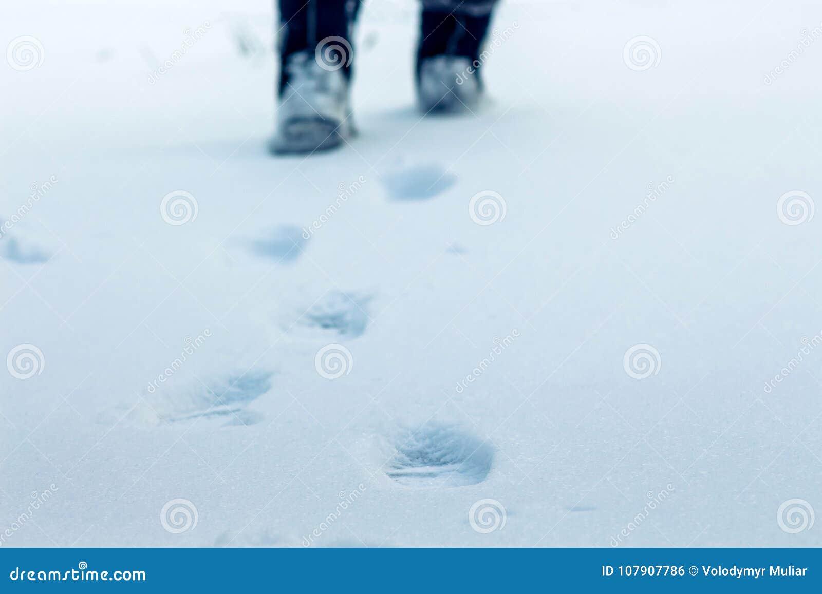 Un jour d hiver sur les traces de neige des jambes humaines soyez évident, dedans
