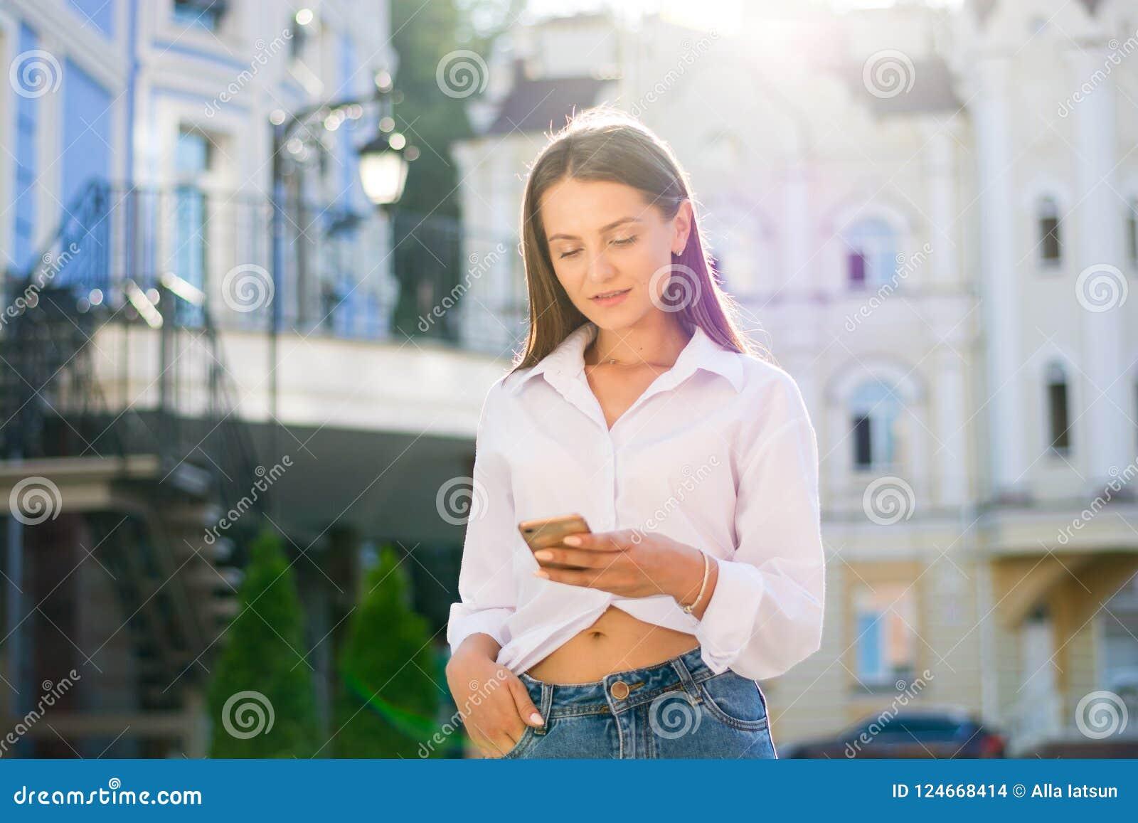 Un joven, muchacha de moda vestida con un smartphone en un st de la ciudad