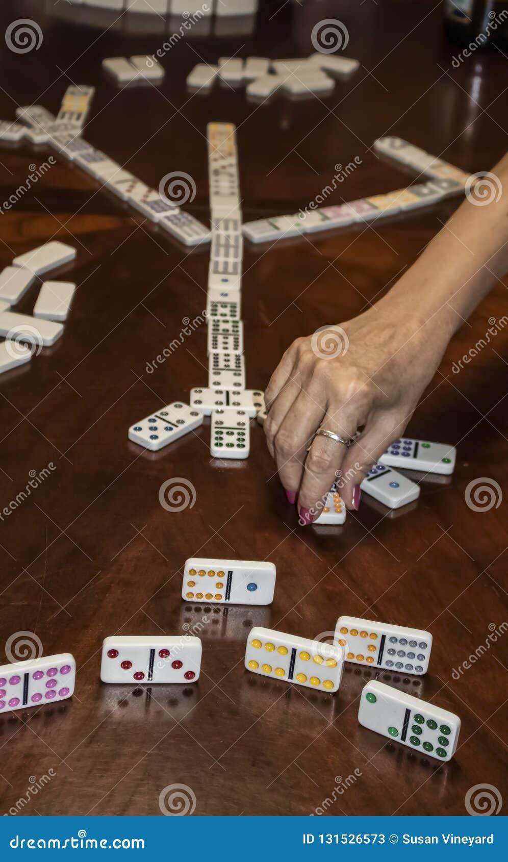 Un juego de los dominós de la garra del pollo con una mano que juega una teja y que muestra a personas una pedazos del juego con