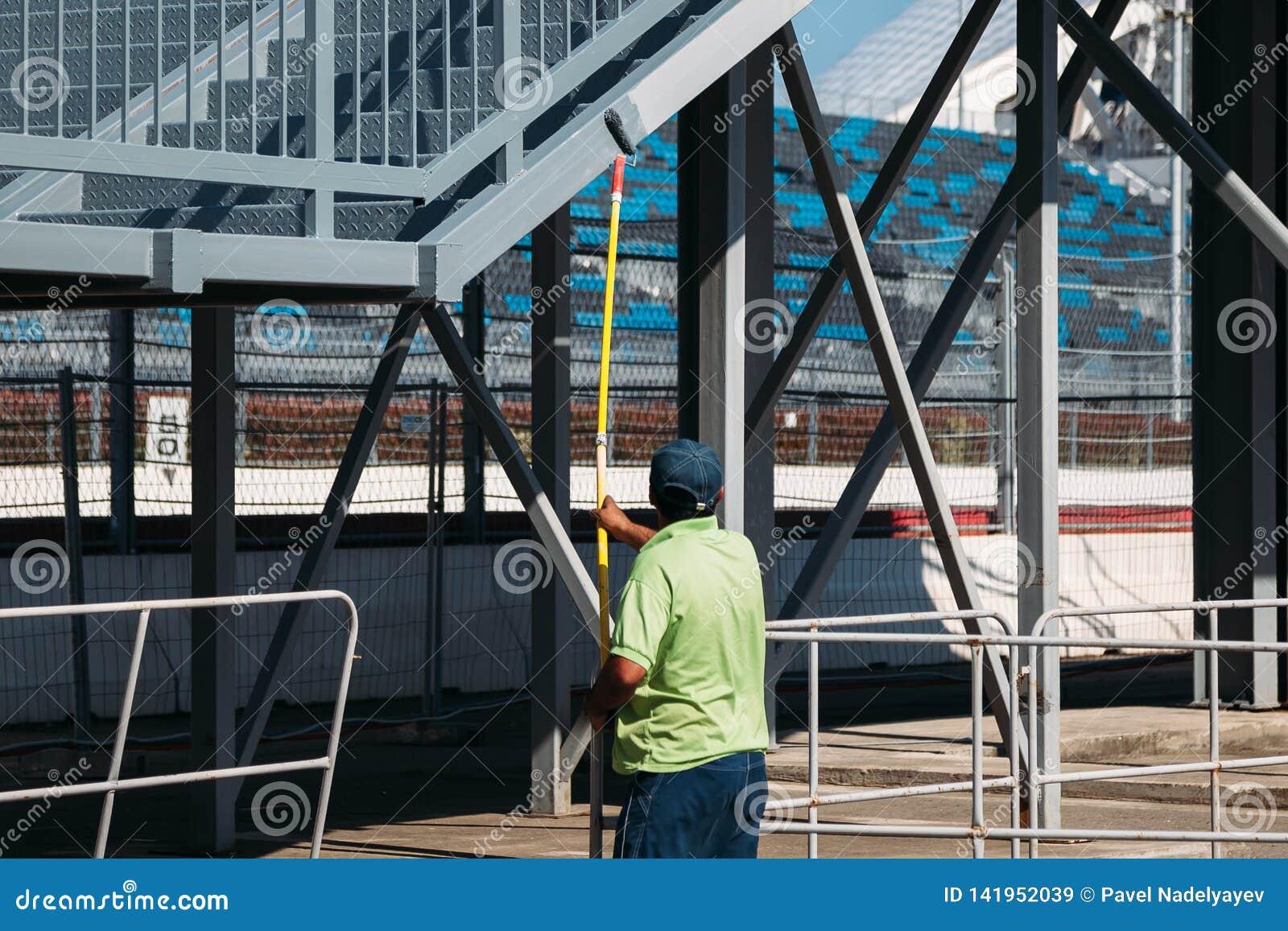 Un lavoratore con una pittura con un rullo dipinge un ponte pedonale