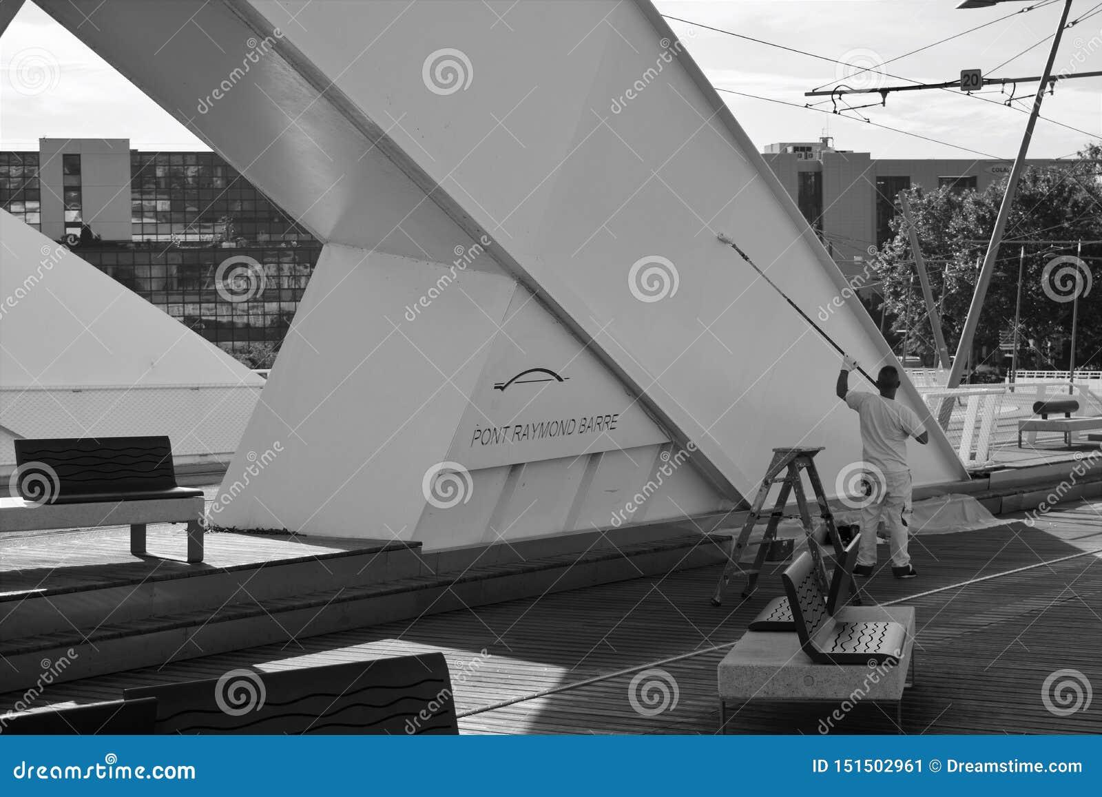Un lavoratore ridipinge un ponte