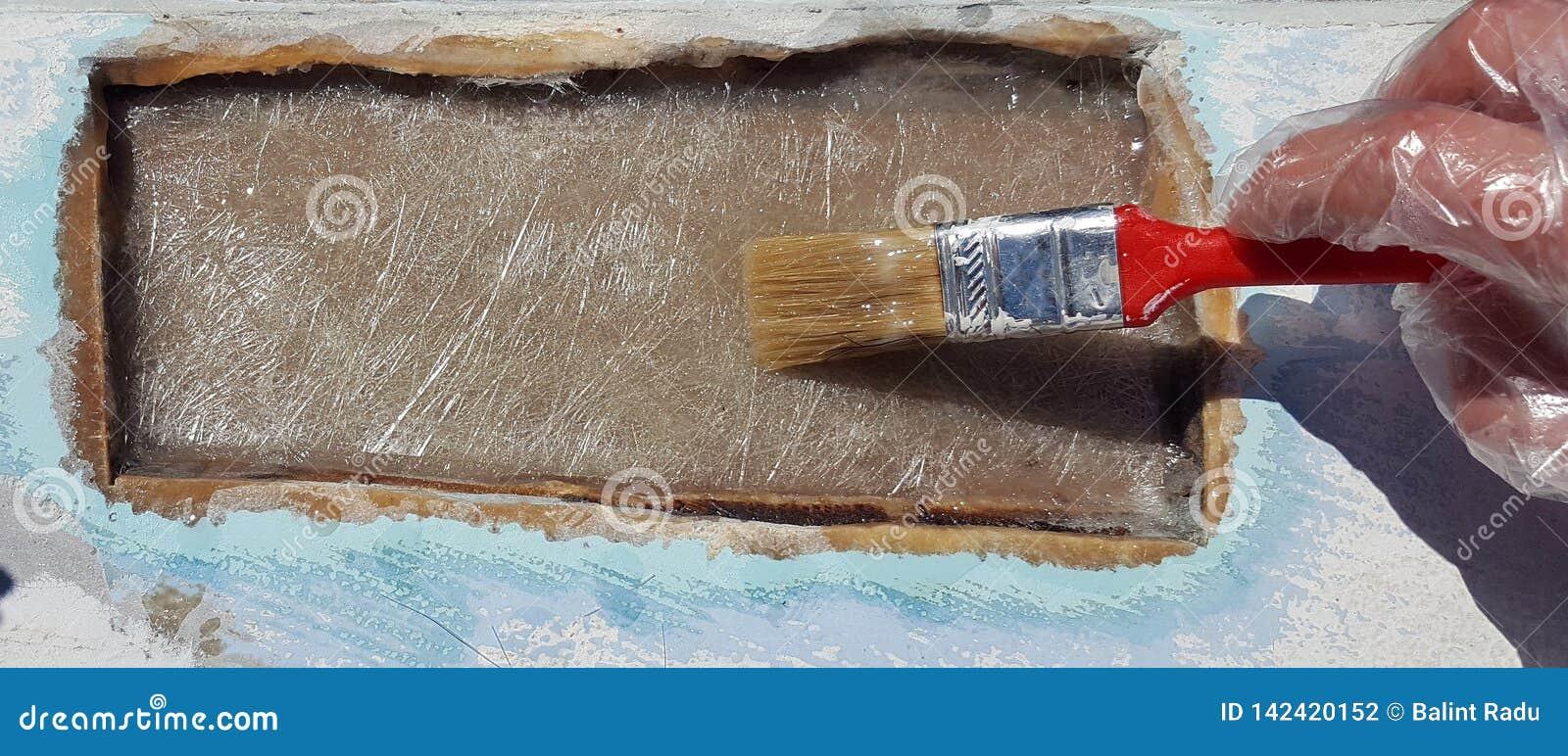 Un lavoratore sta applicando la resina per la riparazione del foro