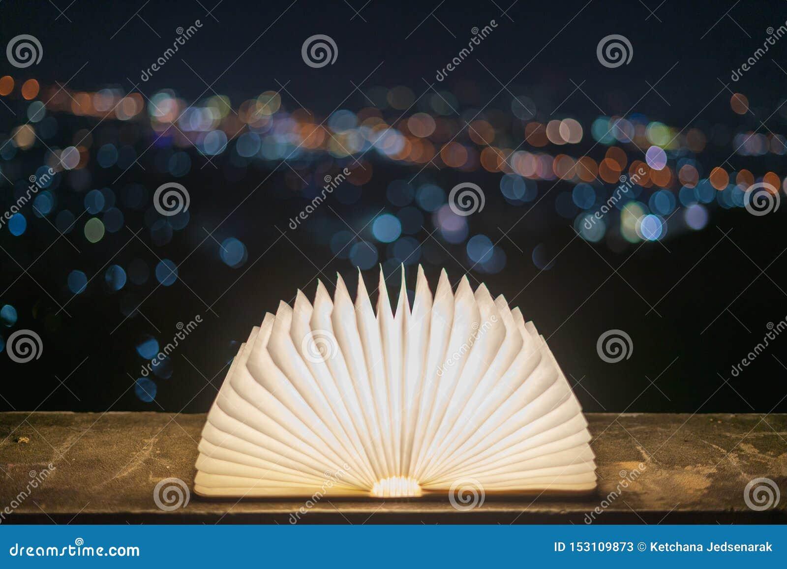 Un libro che si apre con luce su una carta come magia, disposto su un pavimento del cemento con un fondo del bokeh per il Natale