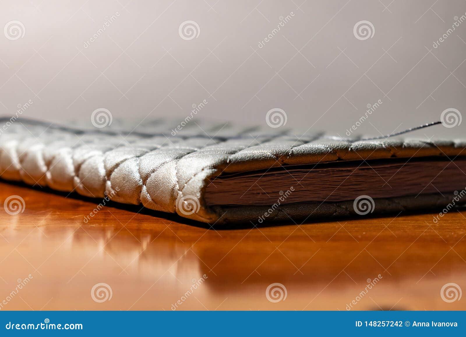 Un libro, un cuaderno con un modelo a cuadros en una tabla de madera en diversas actitudes La cubierta es gris y suave con textur