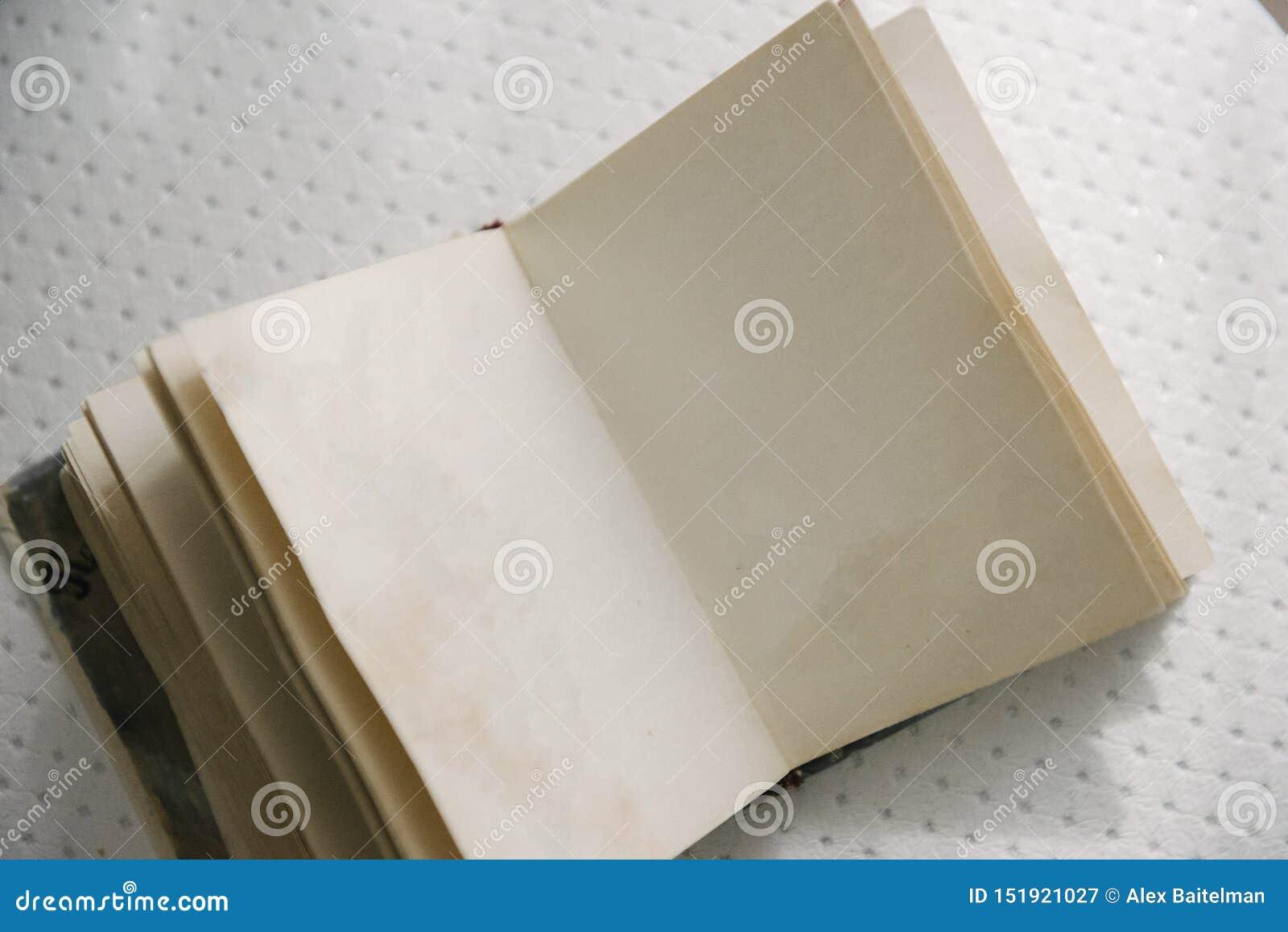 Un libro en blanco abierto está en la tabla Un libro abierto con las páginas en blanco está en la tabla