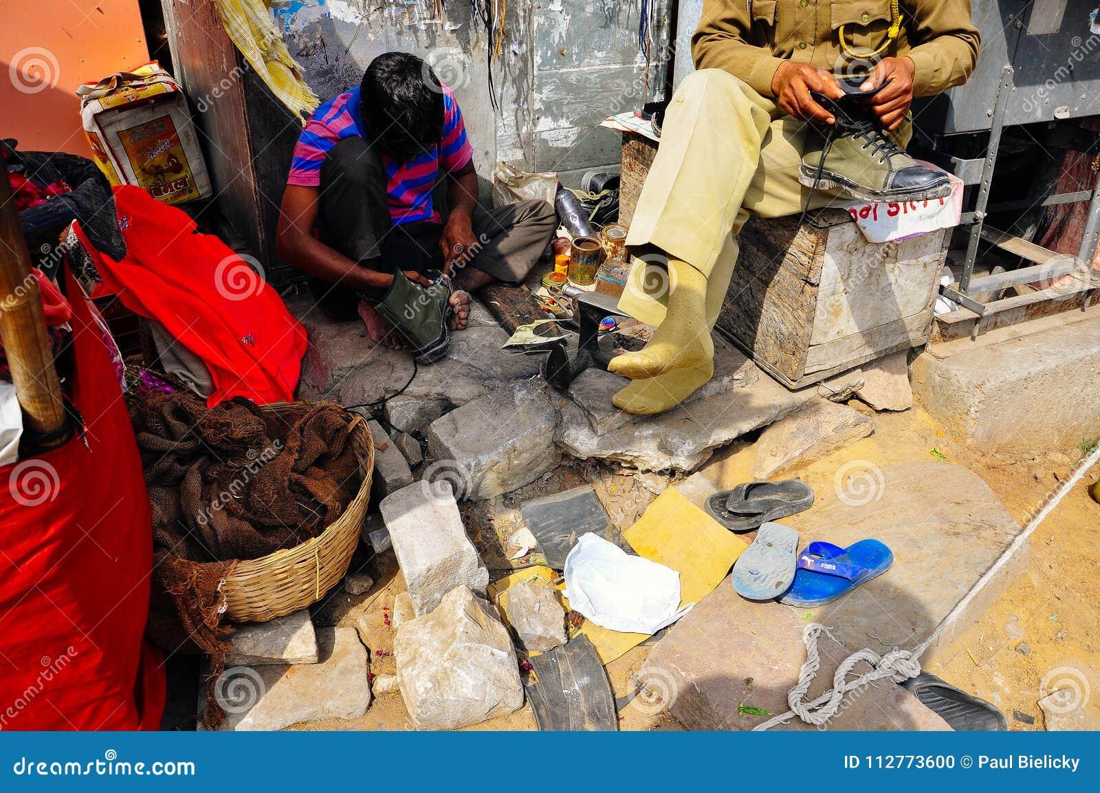 Un local repara un zapato del ` s del hombre en Jaipur, la India