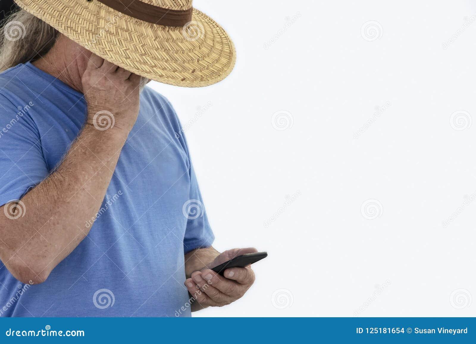 Un más viejo hombre cabelludo gris largo en sombrero de paja ancho del borde y la camiseta sombrean sus ojos para ver el teléfono