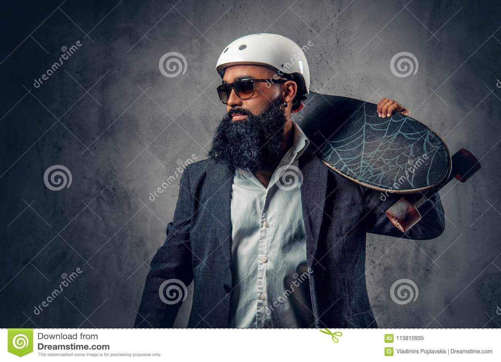 Un maschio alla moda si è vestito nelle tenute grige di un vestito lungamente imbarca
