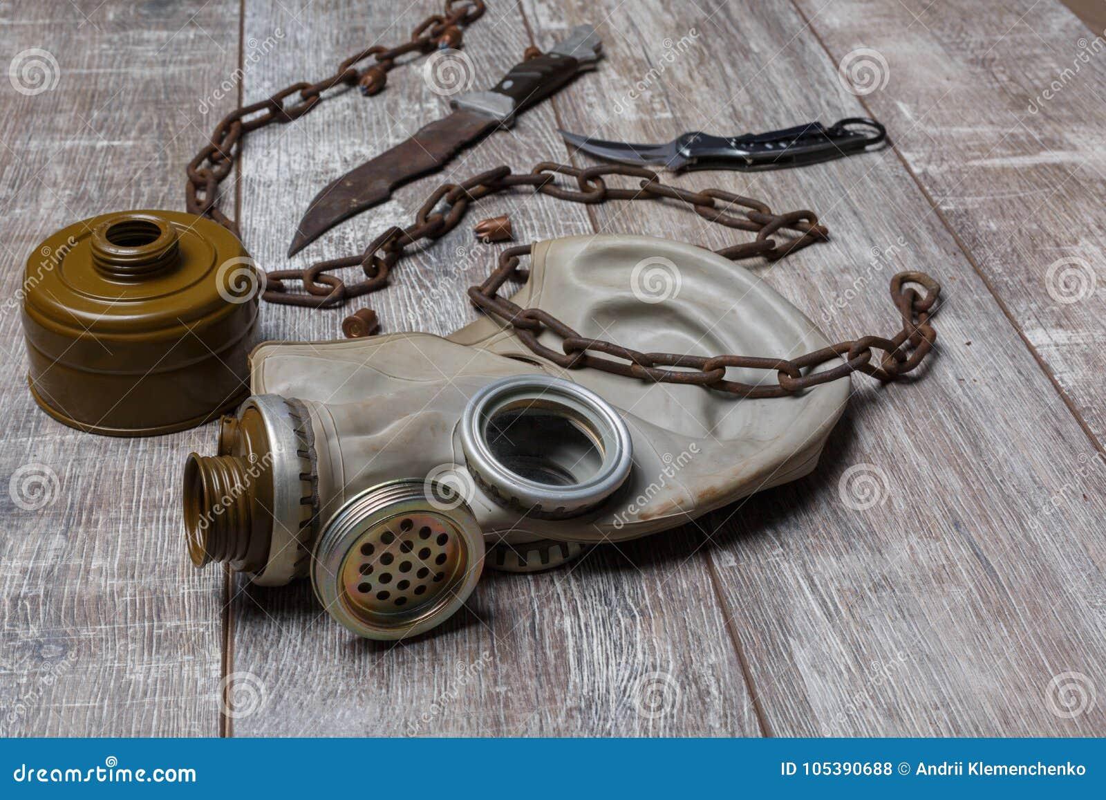Un masque de gaz démonté avec une chaîne avec des couteaux sur un plancher en bois Vue sous un angle