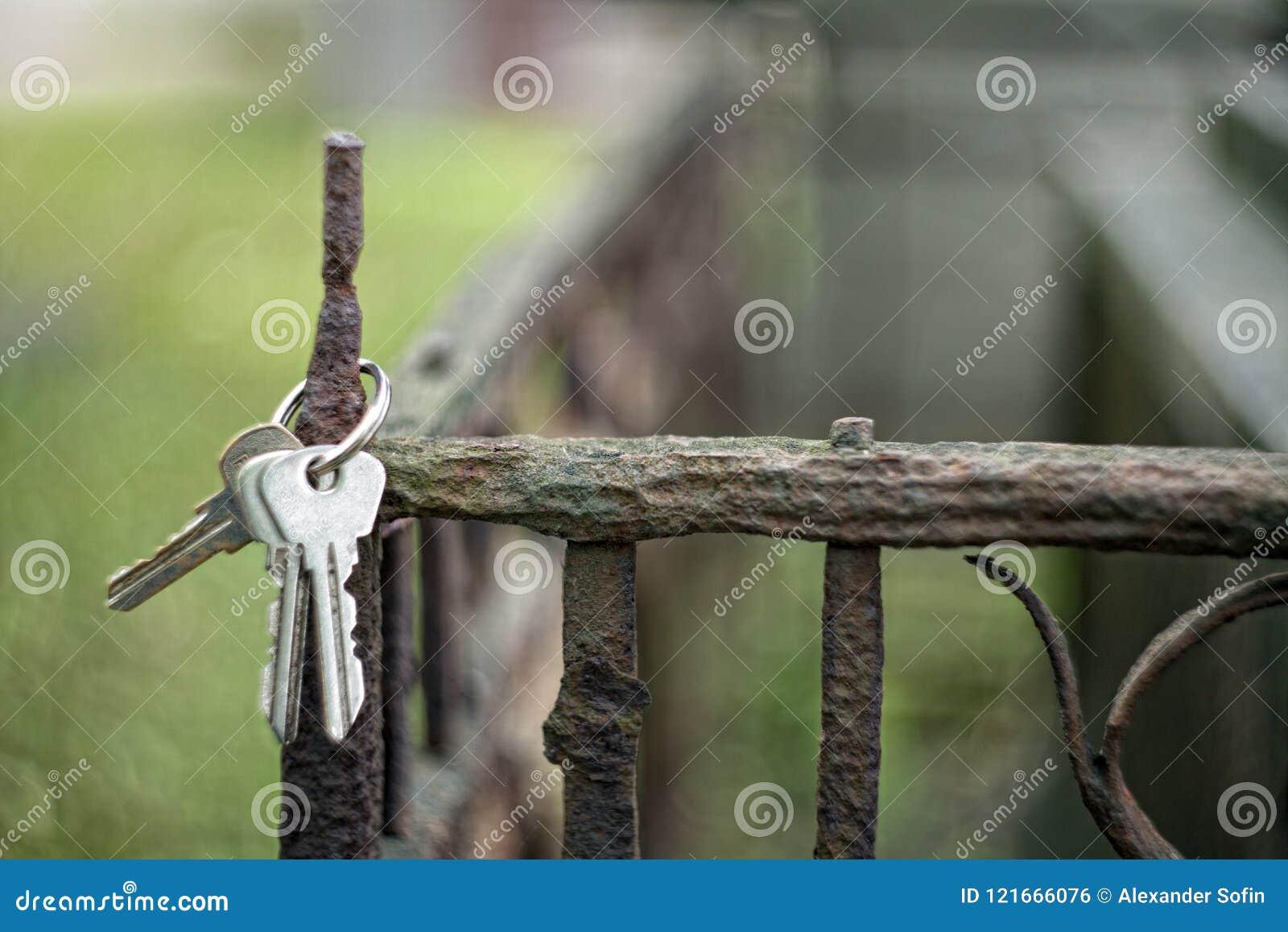 Un mazzo di chiavi che appendono sul recinto arrugginito della tomba in