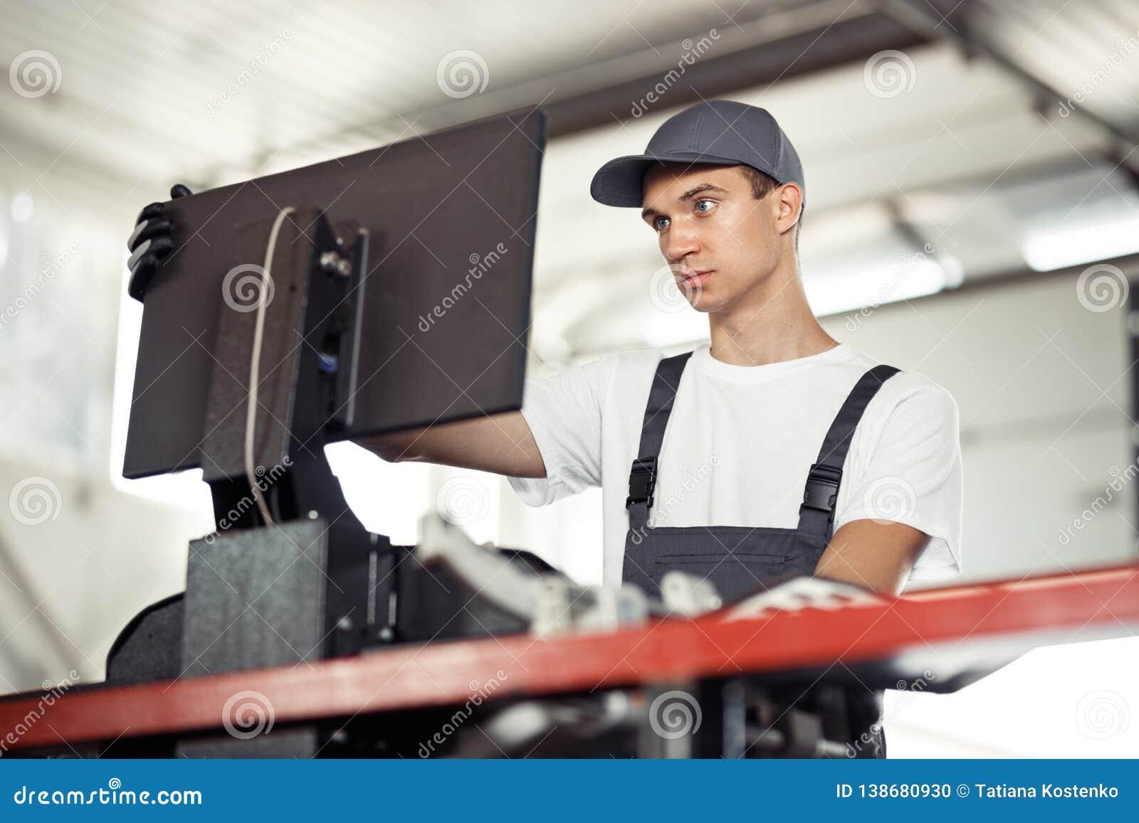 Un mecánico de ojos azules joven está comprobando un coche en un servicio del coche usando un ordenador