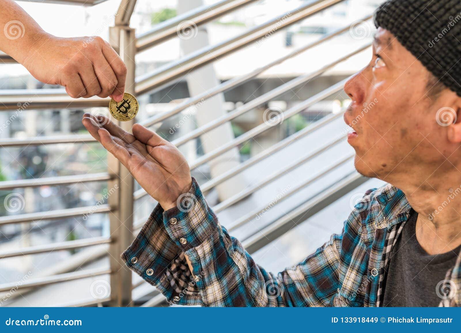 Un mendiant sans abri masculin recevant une pièce de monnaie de bitcoin d or