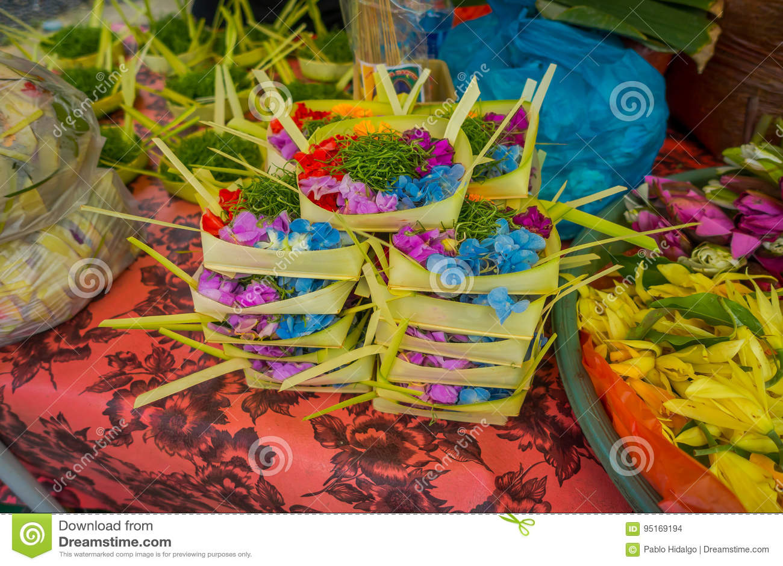 Un mercado con una caja hecha de hojas, dentro de un arreglo de flores en una tabla, en la ciudad de Denpasar en Indonesia