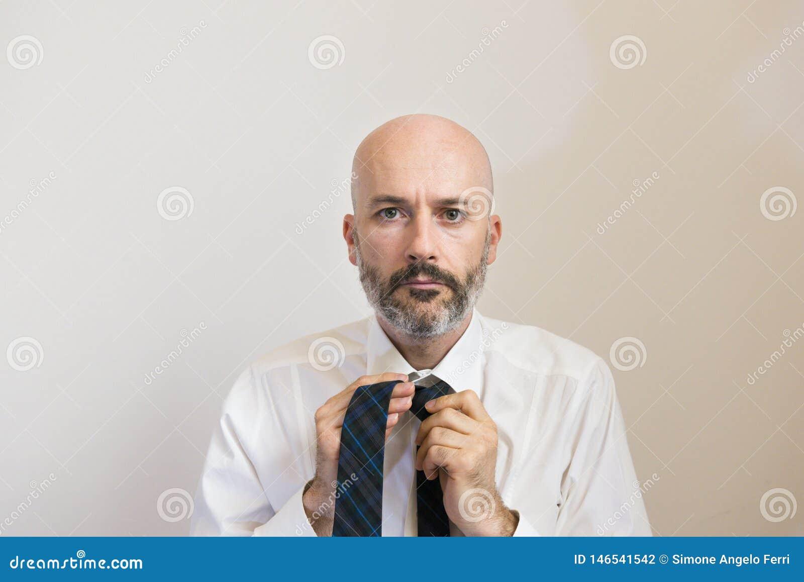 Un metà di uomo dell età con la barba sta annodando la sua cravatta