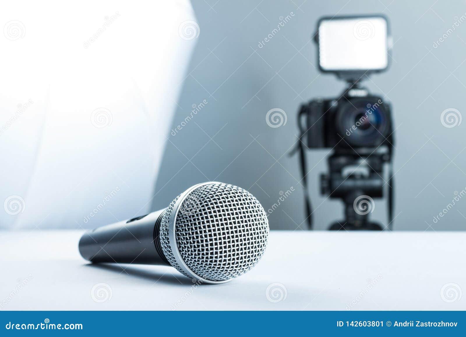 Un microfono senza fili che sta su una tavola dello studio contro lo sfondo della macchina fotografica di DSLR alla luce e al sof
