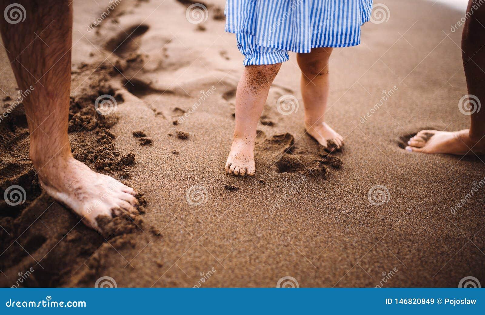 Un midsection de padres con la hija del niño stabding en la playa el vacaciones de verano