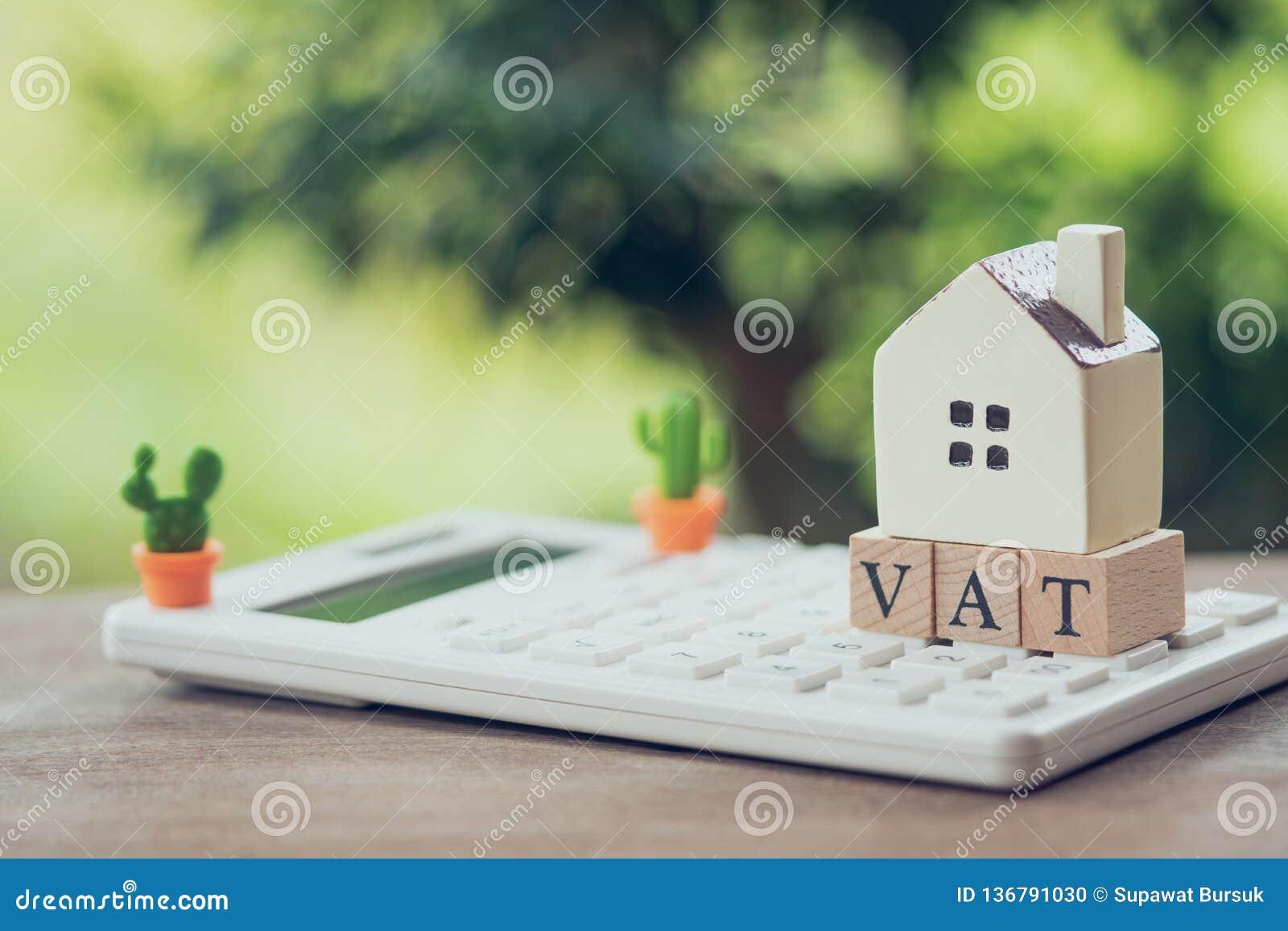 Un modelo modelo de la casa se pone en la palabra de madera IVA como concepto de las propiedades inmobiliarias de la propiedad de
