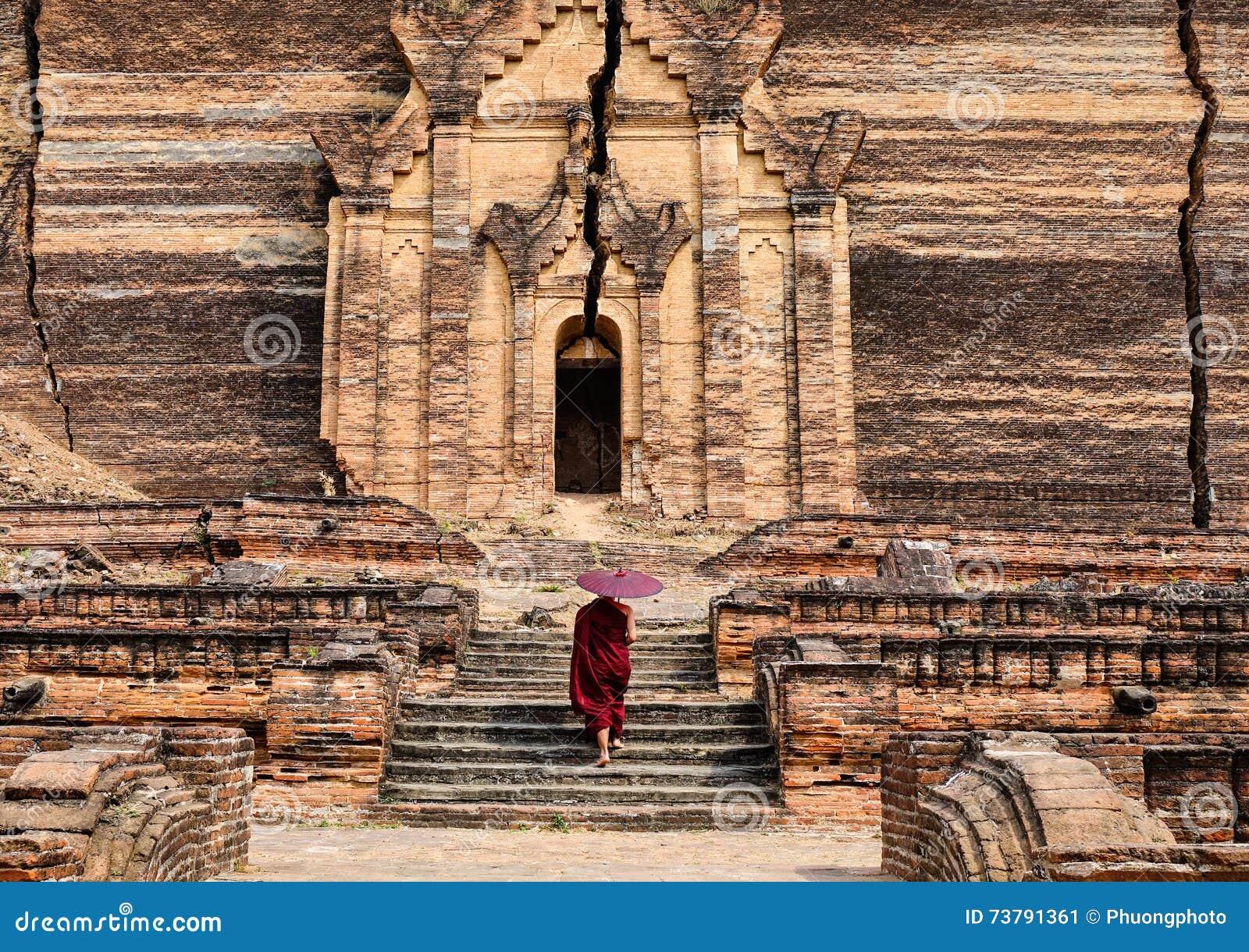 Un monje que viene a la pagoda antigua en Mandalay, Myanmar