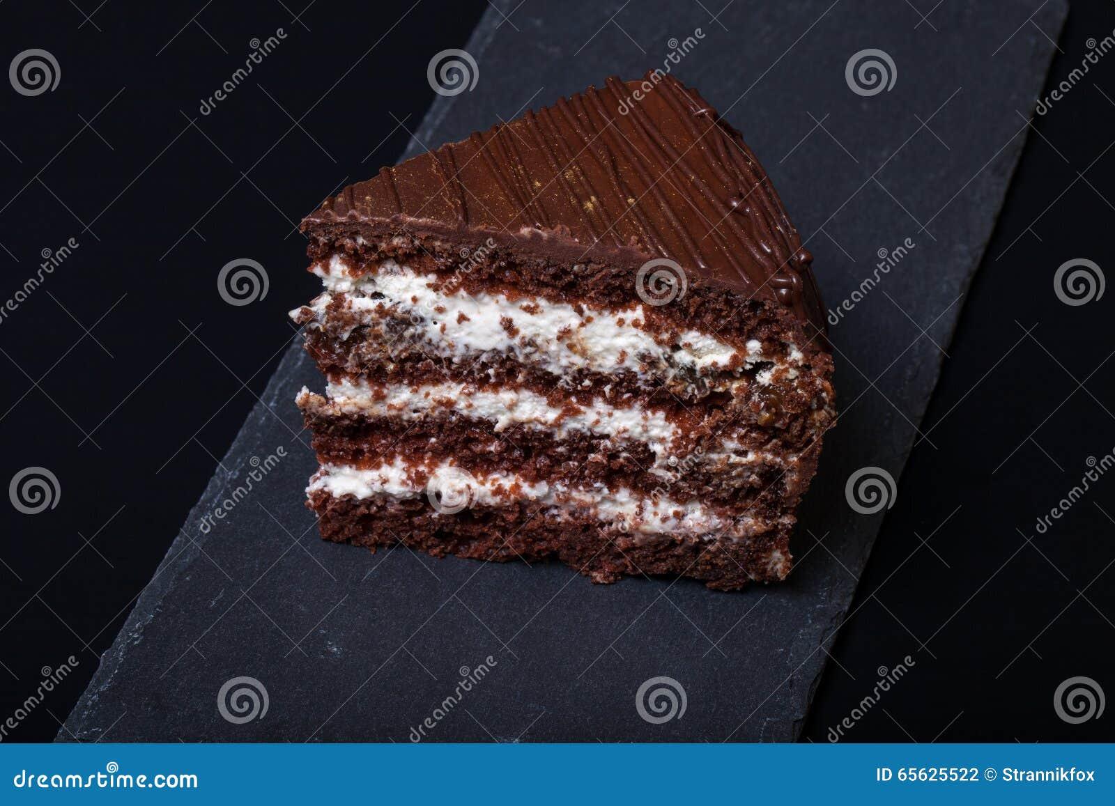 Un morceau de gâteau de chocolat de plat d ardoise sur le fond noir