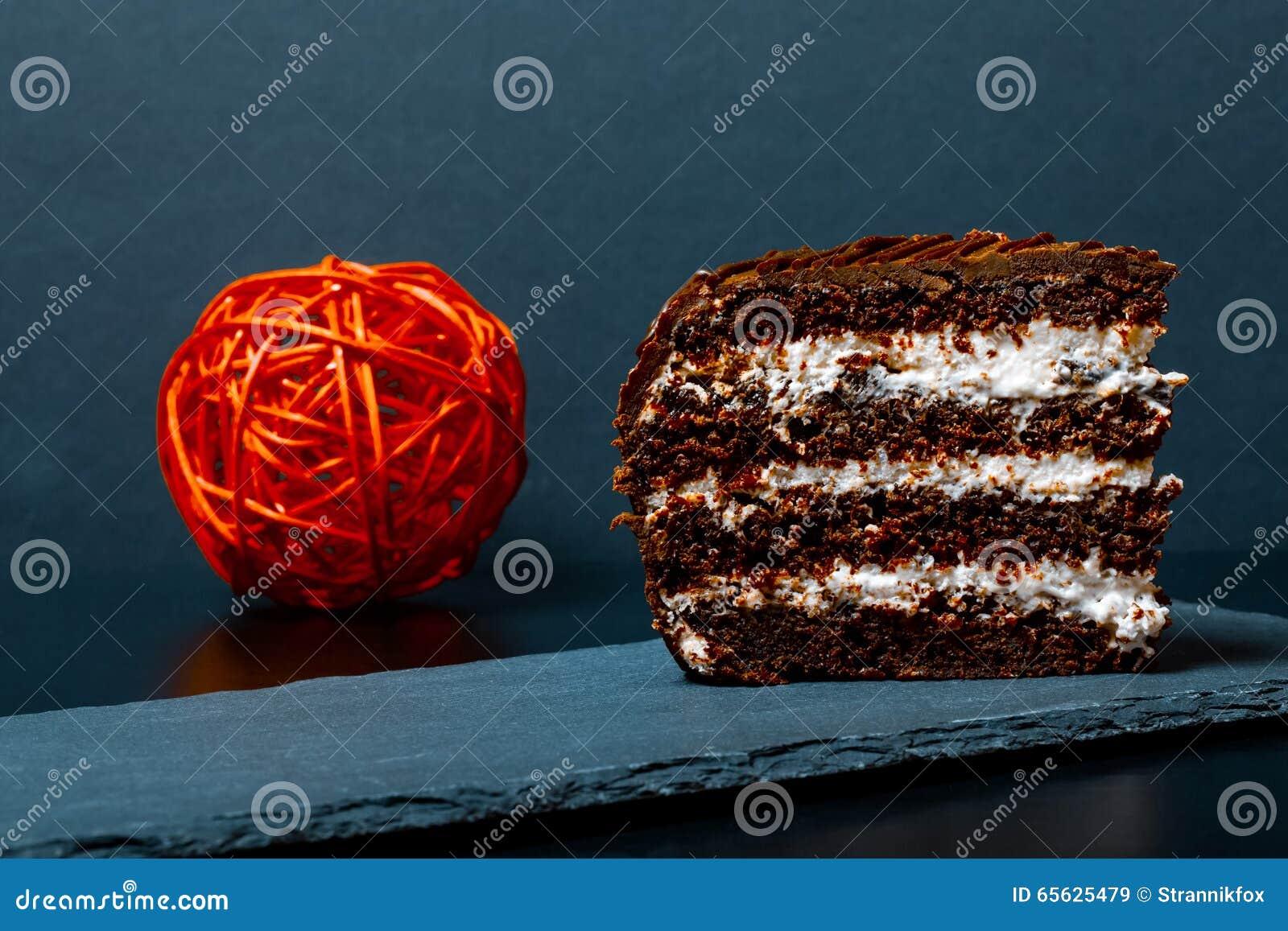 Un morceau de gâteau de chocolat de plat d ardoise sur le fond noir Se