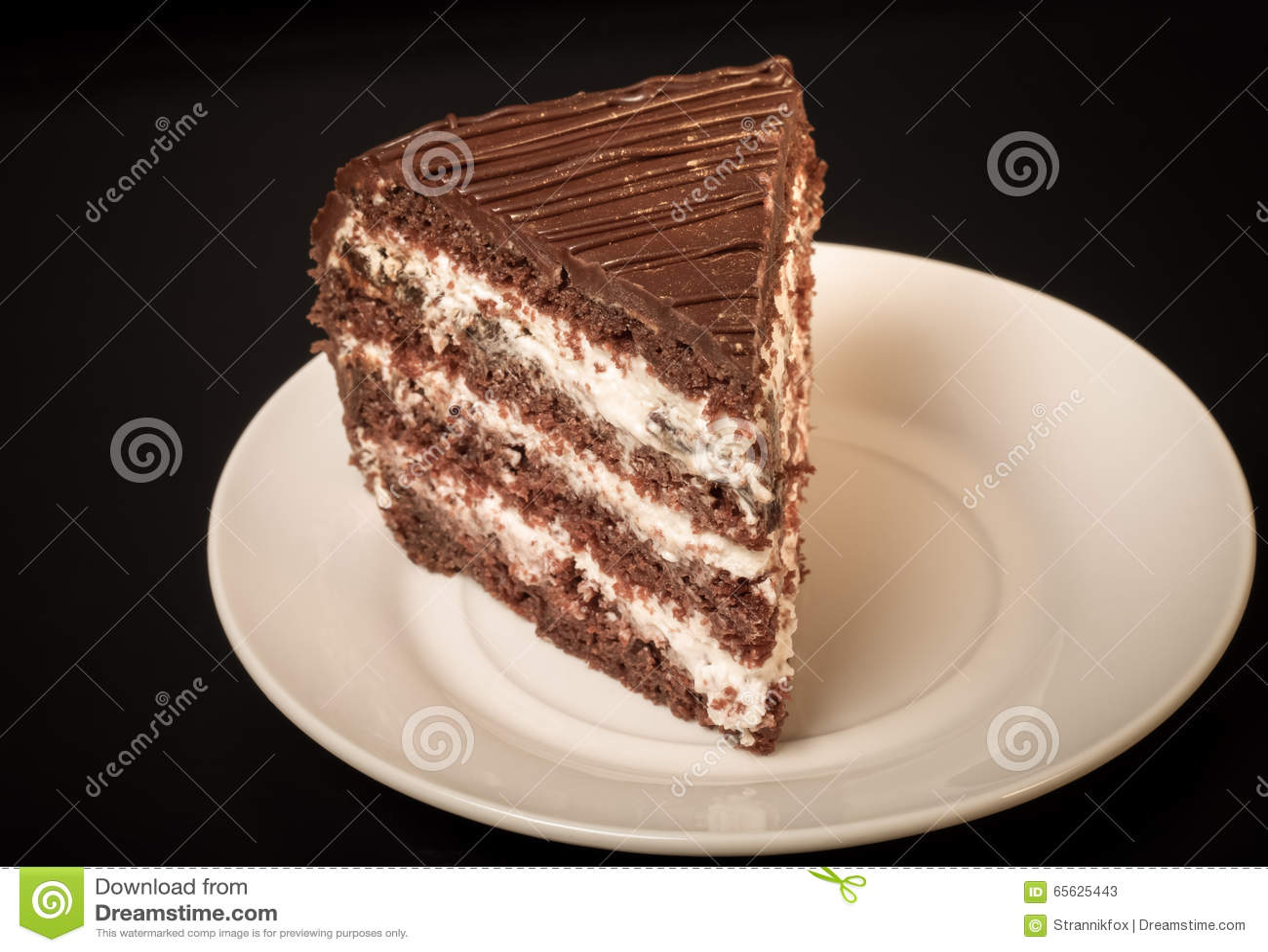 Un morceau de gâteau de chocolat du plat blanc sur le fond noir À
