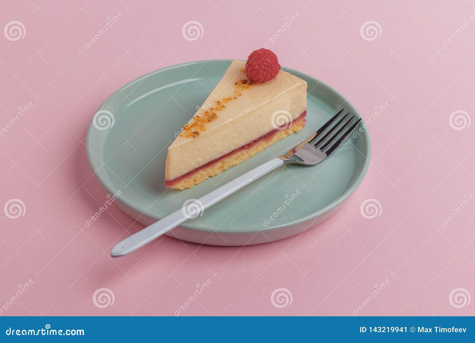 Un morceau du gâteau, gâteau au fromage d un plat avec une fourchette sur un fond rose