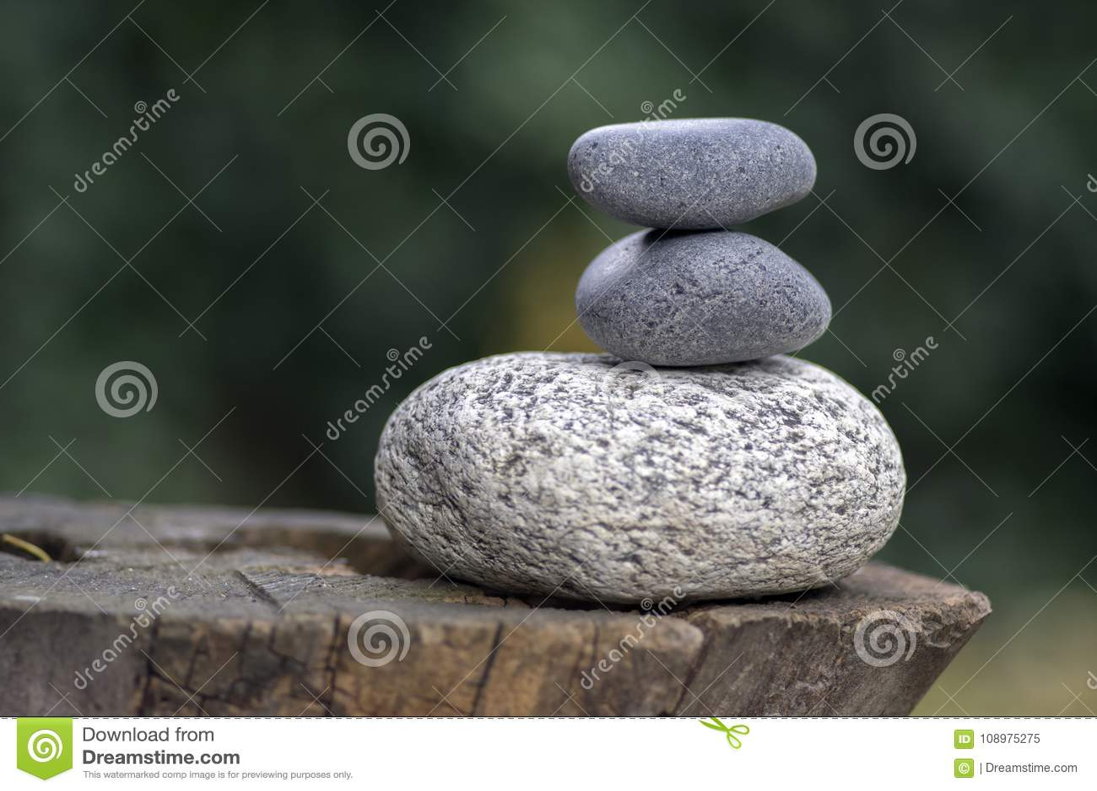 Un mucchio di tre pietre di zen sui ciottoli bianchi e grigi di legno del ceppo, di meditazione si eleva