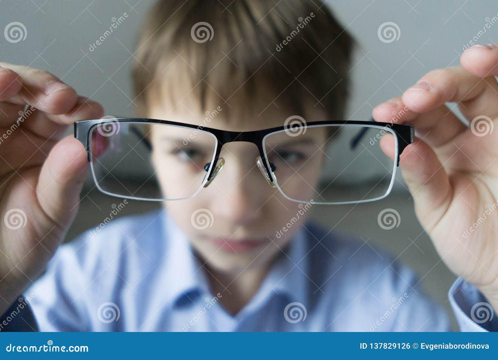 Un muchacho de 9 años en una camisa azul con los vidrios comprueba su vista Descontentado con el hecho que prescribió los vidrios