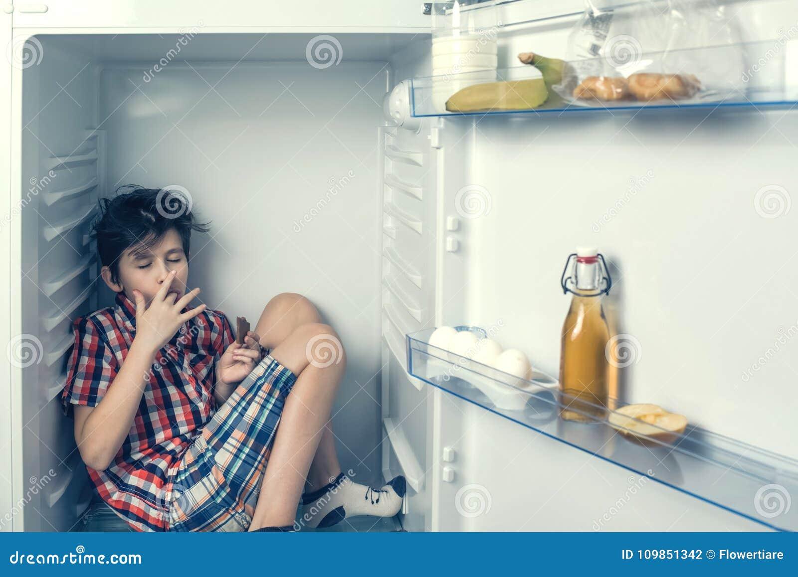Un muchacho en una camisa y pantalones cortos que come una barra de chocolate dentro de un refrigerador con la comida