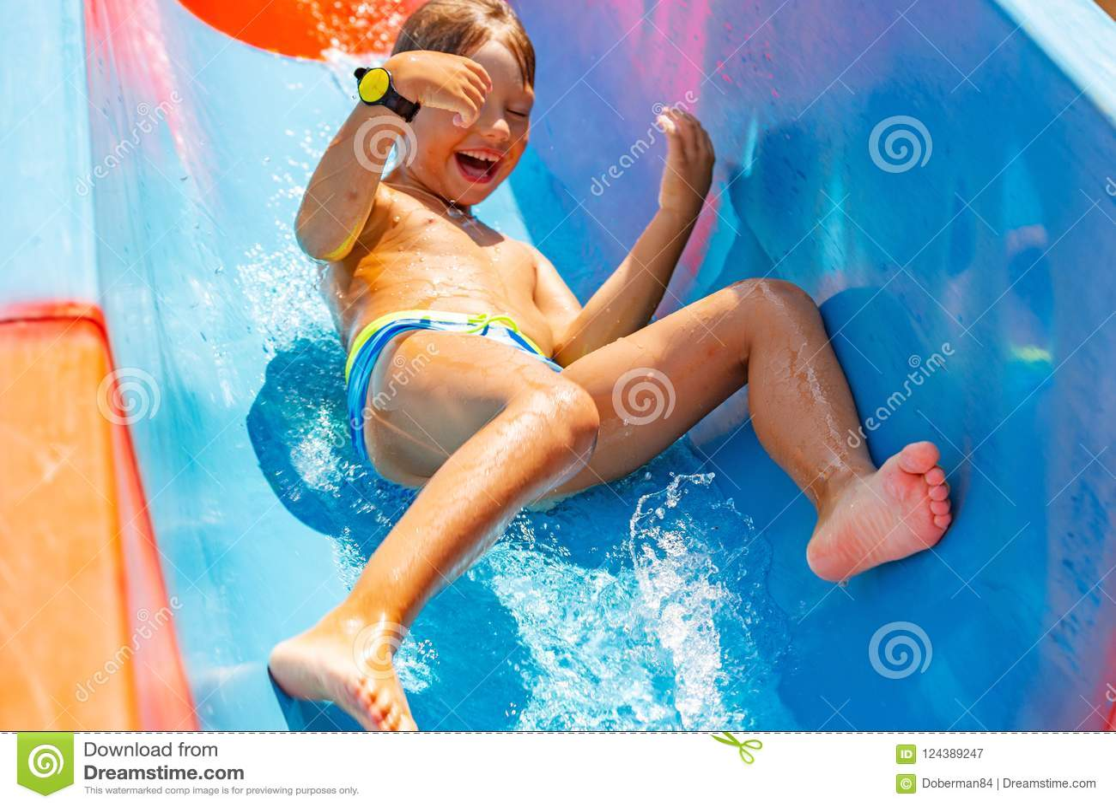 Un muchacho feliz en el tobogán acuático en una piscina que se divierte durante vacaciones de verano en aguamarina hermosa parque