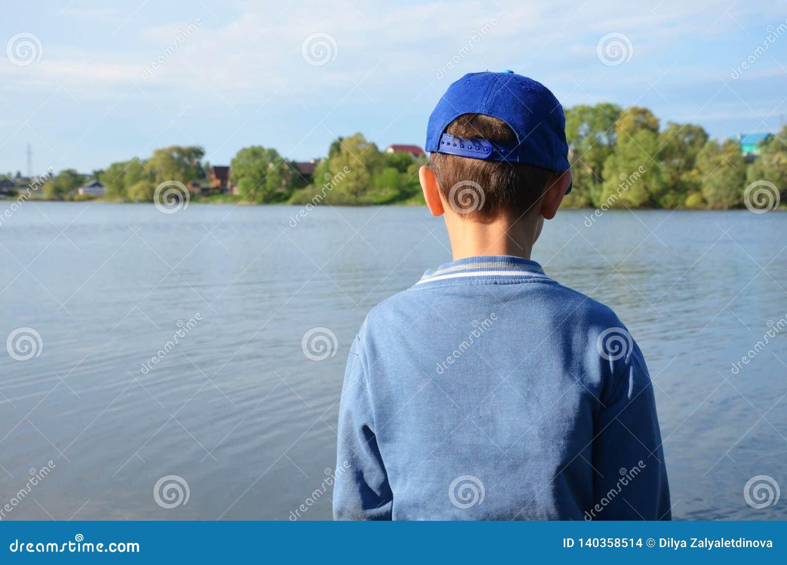 Un muchacho hace una pausa el lago y las miradas del bosque en el agua tranquila Naturaleza, reflexi?n, inspiraci?n, al aire libr