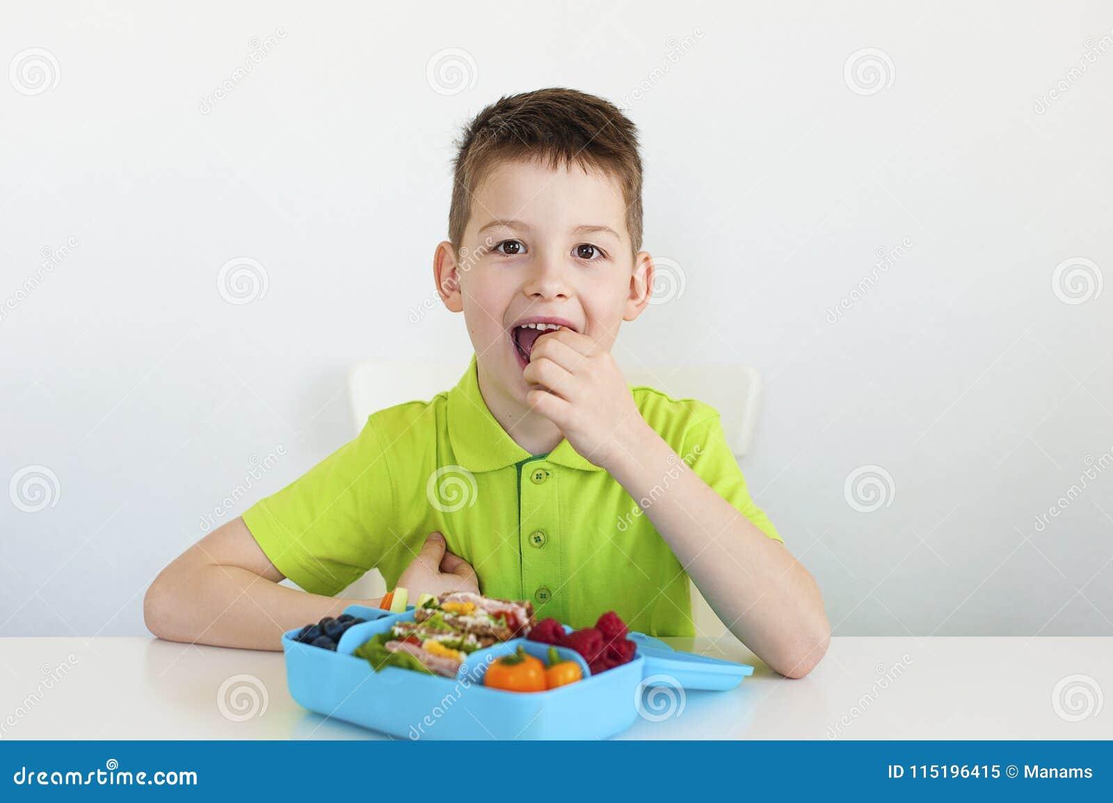 Un muchacho joven que come un almuerzo escolar sano