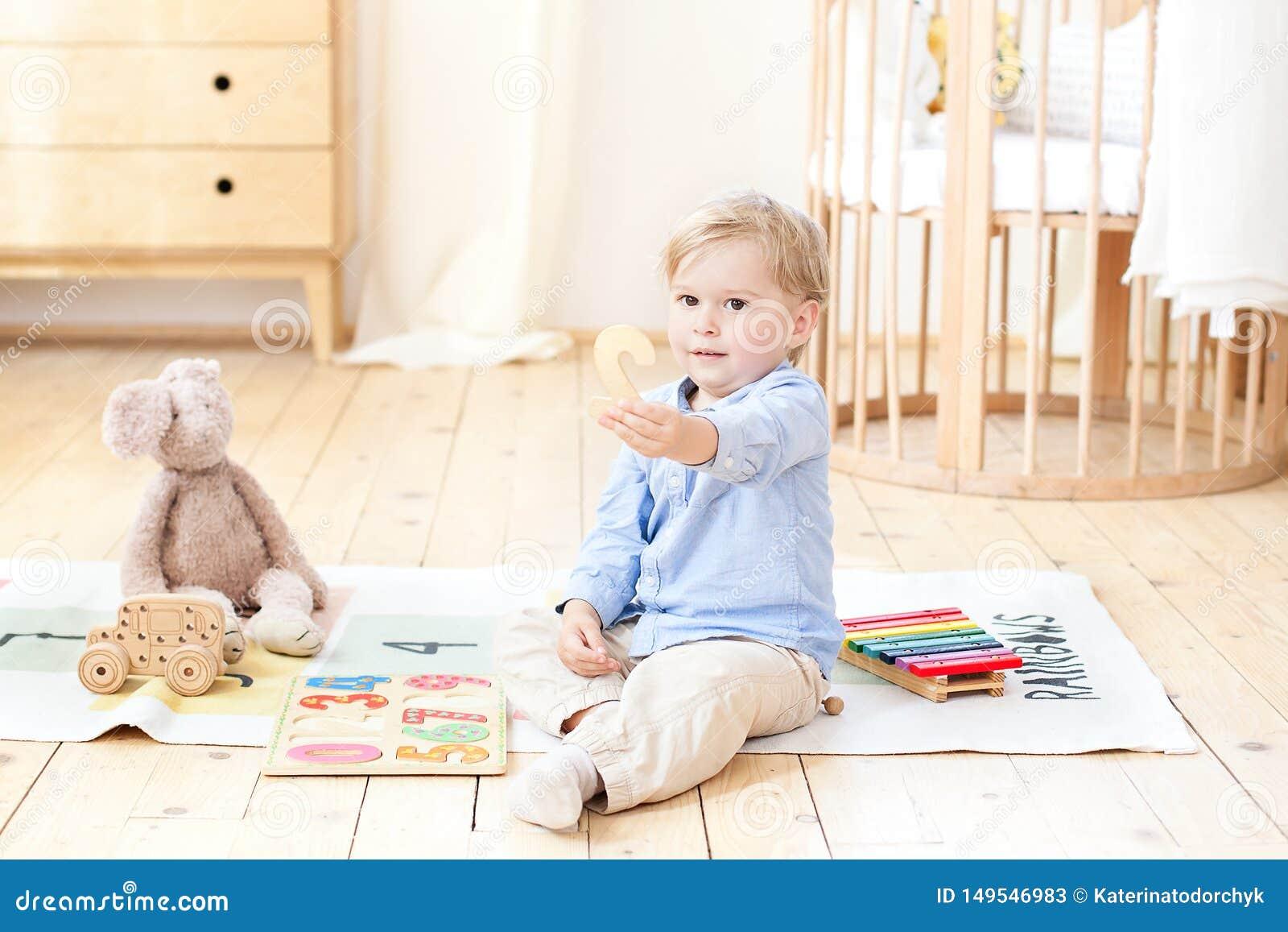 Un muchacho juega con los juguetes de madera y muestra el n?mero 2 Juguetes de madera educativos para un ni?o Retrato de un mucha