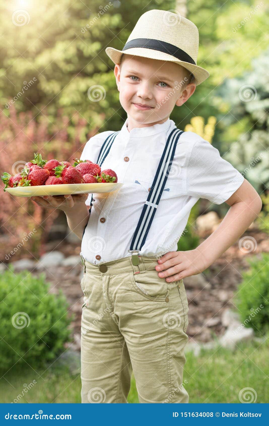 Un muchacho sostiene una placa de la fresa aromática madura