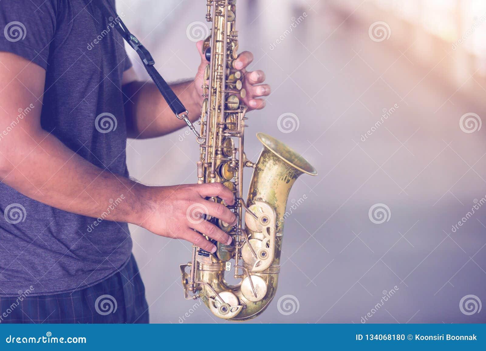 Un musicista della via gioca il sassofono con la gente confusa