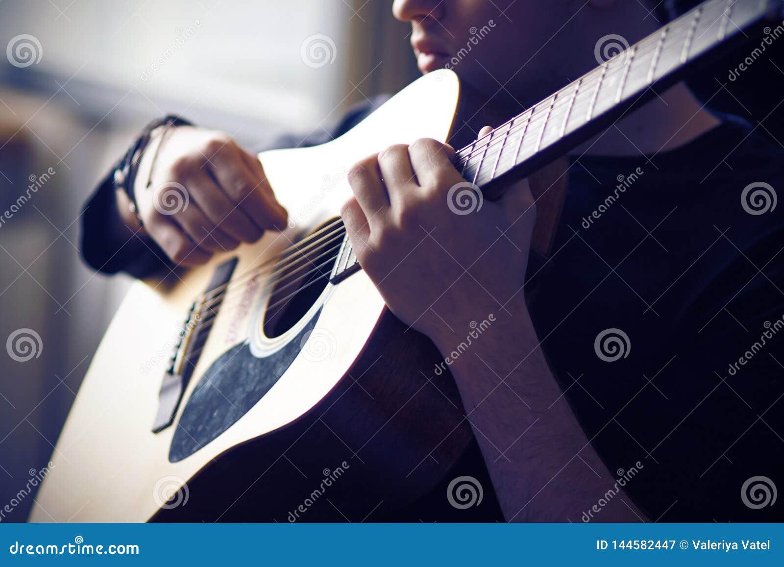 Un musicista gioca la sua chitarra acustica, tenente il fretboard alla base