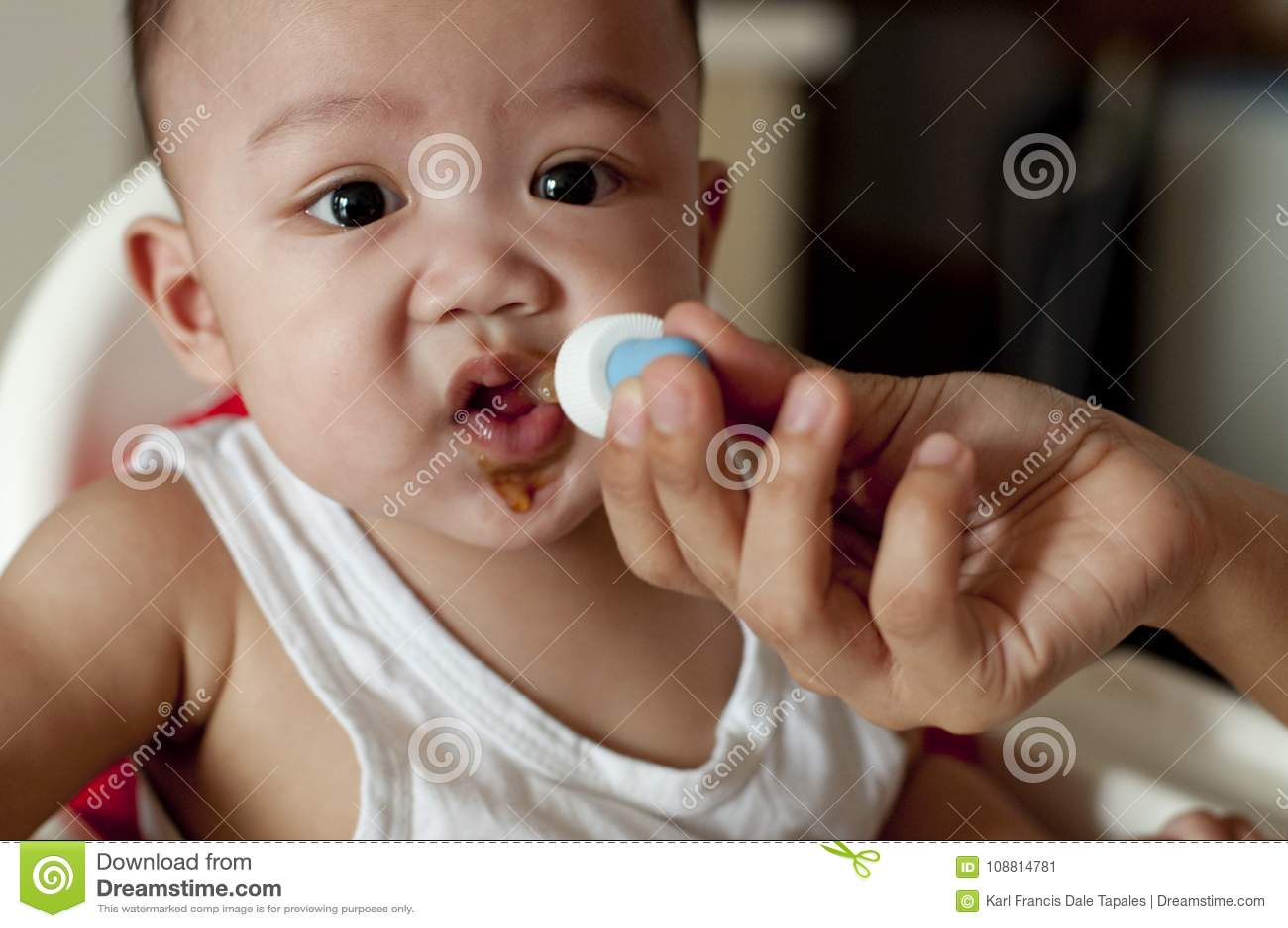 Un neonato sta bevendo le sue vitamine facendo uso di un contagoccia